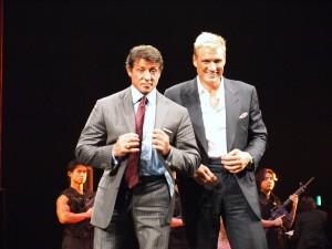 ステージ上でポーズをとるスタローンとラングレン